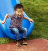 Boy smiling on slide