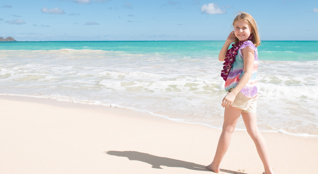 girl smiling standing on the shore of a beach